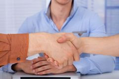 Businessmen shaking hands in office Stock Photo