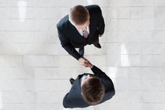 Businessmen Shaking Hands In Office Stock Images
