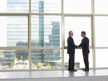 Businessmen Shaking Hands In Office. Full length side view of businessmen shaking hands in office building Royalty Free Stock Photo