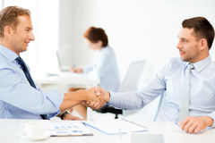 Businessmen shaking hands in office Royalty Free Stock Photography