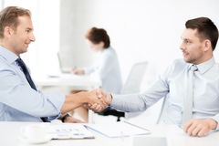 Businessmen shaking hands in office Stock Image