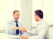 Businessmen shaking hands in office Royalty Free Stock Photo