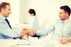 Businessmen shaking hands in office Royalty Free Stock Images