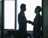 Businessmen shaking hands in office, Silhouette Stock Photos