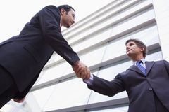 Businessmen shaking hands outside office building. Businessman shaking hands outside modern office building Royalty Free Stock Images