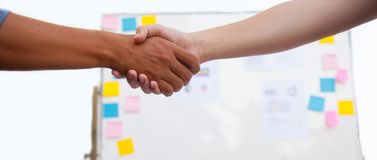 Businessmen shaking hands over table in the meeting with copy space with whiteboard full of sticky note and chart background stock photo