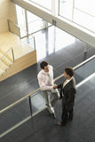 Businessmen Shaking Hands By Railing In Office Royalty Free Stock Photography