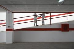 Businessmen Shaking Hands On Ramp In Parking Garage Stock Image