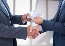 Businessmen shaking hands and receiving money. Mid section of businessmen shaking hands and receiving money Stock Photos