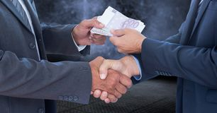 Businessmen shaking hands and receiving money. Mid section of businessmen shaking hands and receiving money against digitally composite background Royalty Free Stock Photos