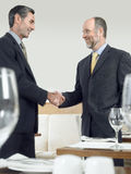 Businessmen Shaking Hands In Restaurant Royalty Free Stock Images