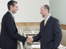 Businessmen Shaking Hands In Restaurant Stock Images