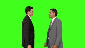 Businessmen shaking hands and smiling. On green screen background stock footage