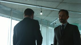 Businessmen shaking hands and smiling. Handsome businessmen communicating about their enterprise, company or firm, shaking hands, smiling and going away while stock video footage