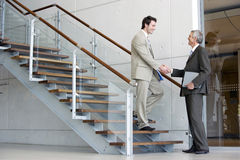 Businessmen shaking hands on steps Royalty Free Stock Image