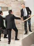 Businessmen shaking hands on steps Royalty Free Stock Images