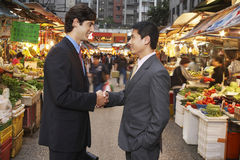 Businessmen Shaking Hands At Street Market. Side view of young businessmen shaking hands at street market Royalty Free Stock Photos