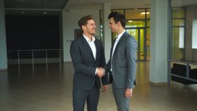Businessmen shaking hands. Two confident businessmen shaking hands and smiling. Two businessmen met in the office and shake hands,two businessman shake hands in stock footage