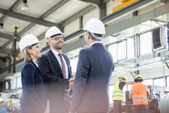 Businessmen shaking hands with workers working in background at metal industry royalty free stock images
