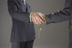 Businessmen Shaking Hands Wrapped In Gold Chain And Padlock Royalty Free Stock Photos