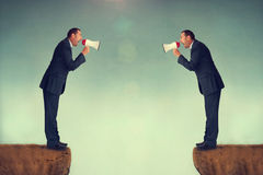 Businessmen shouting. Businessman shouting at each other through loudhailers or megaphones Royalty Free Stock Image