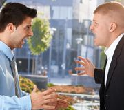 Businessmen shouting in front of office Stock Photos