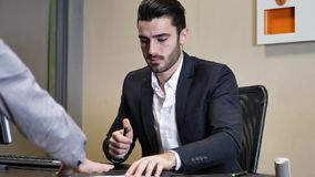 Businessmen signing contract or document. Handsome businessman at desk in his office, receiving document or contract and signing it with a pen, talking to client stock video