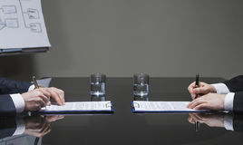 Businessmen signing contracts. Business people signing contracts in meeting room stock image