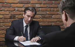 Businessmen signing contracts Stock Images