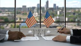 Businessmen signing papers at table. Men shake hands near flags. Common goals in politics. Work of US government stock footage