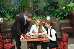Businessmen sitting in cafe for a laptop. two girls. Waitress taking order from businessmen in cafe smiling laptop work Royalty Free Stock Images