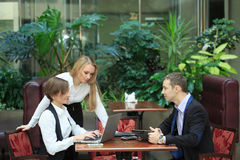 Businessmen sitting in cafe for a laptop. Waitress taking order from businessmen in cafe smiling laptop work Stock Images