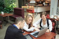 Businessmen sitting in cafe for a laptop. Waitress taking order from businessmen in cafe smiling laptop work Stock Photo