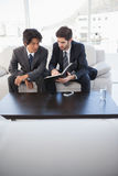 Businessmen sitting on couch together Royalty Free Stock Photos