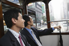 Businessmen Sitting In Double Decker Tram. Side view of two businessmen sitting in double decker tram Royalty Free Stock Image