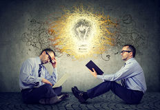 Businessmen sitting on a floor in office using laptop reading a book with light bulb idea thoughts Royalty Free Stock Photos