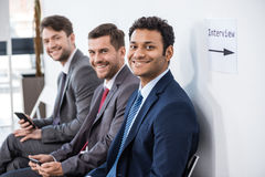 Businessmen sitting in queue and waiting for interview in office Stock Photo