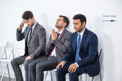 Businessmen sitting in queue and waiting for interview in office Stock Photos