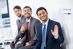 Businessmen sitting in queue and waiting for interview in office Stock Image