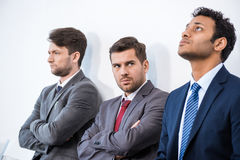 Businessmen sitting in queue and waiting for interview in office Stock Photography
