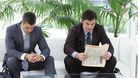 Businessmen sitting on sofa. Reading a newspaper while they are waiting for interviews. Footage in High definition stock video