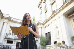 Businesswoman with folder. Businessmen sitting together while businesswoman writes in a filofax in a coffee terrace set in a colonial building Royalty Free Stock Photos