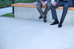 Businessmen sitting on wall Royalty Free Stock Photos