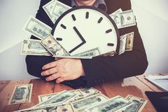 Businessmen are sitting at the working table and holding clock a. Nd money; time are worth royalty free stock images