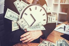 Businessmen are sitting at the working table and holding clock a. Nd money; time are worth stock images