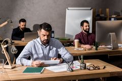 businessmen sitting at working tables with different royalty free stock images