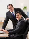Businessmen smiling at desk in office Stock Image