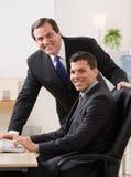 Businessmen smiling at desk in office. Confident businessmen smiling at desk in office Stock Image