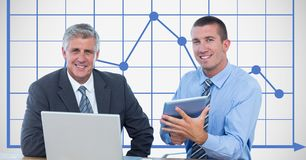Businessmen smiling while using technologies against graph royalty free stock image