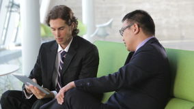 Businessmen On Sofa And Using Digital Tablet. Businessmen sit and have informal meeting looking at data on digital tablet together.Shot on Canon 5d Mk2 with a stock video